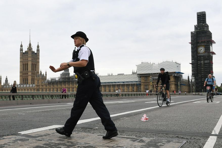 A police woman patrols on Westminster Bridge after a car crashed into security barriers outside the Houses of Parliament, in London, Tuesday, Aug. 14, 2018. London police say that a car has crashed into barriers outside the Houses of Parliament and that there are a number of injured. (Stefan Rousseau/PA via AP)