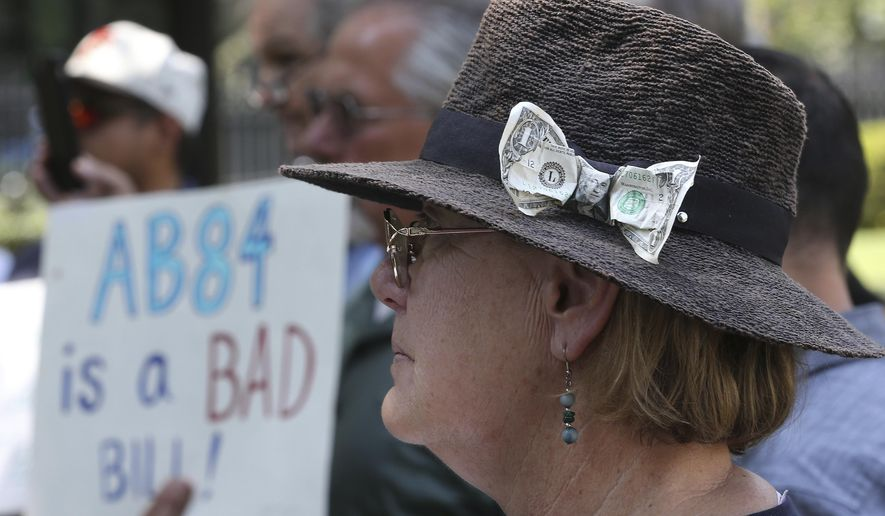 With a dollar bill stuck in her hat, Donna Poulos, of Los Altos, joined other open-government supporters rallying against a measure that would let legislative leaders raise and spend more money to help their preferred candidates, Tuesday, Aug. 14, 2018, in Sacramento, Calif. The bill AB84 by Assemblyman Kevin Mullin, D-South San Francisco, was approved by a state Senate Committee. (AP Photo/Rich Pedroncelli)