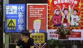 In this Monday, Aug. 13, 2018, photo, a man stands near a poster depicting a mural of U.S. President Donald Trump stating that all American costumers will be charged 25 percent more than others starting from the day president Trump started the trade war against China, on display outside a restaurant in Guangzhou in south China's Guangdong province. The recent trade war between the world's two biggest economies has forced many multinational companies to reschedule purchases and rethink where they buy materials and parts to try to dodge or blunt the effects of tit-for-tat tariffs between Washington and Beijing. (Color China Photo via AP)