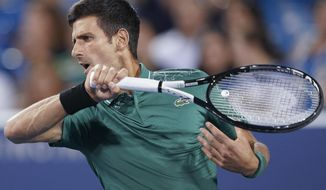 Novak Djokovic, of Serbia, returns to Steve Johnson in the first round at the Western & Southern Open, Monday, Aug. 13, 2018, in Mason, Ohio. (AP Photo/John Minchillo)