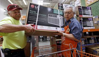 FILE - In this Aug. 1, 2017, file photo, store greeter Danny Olivar, right, lends a hand to a customer to heft an air conditioning unit from a rapidly declining stock at a Home Depot store ahead of an expected heat wave in Seattle. The Home Depot Inc. reports earnings Tuesday, Aug. 14, 2018. (AP Photo/Elaine Thompson, File)