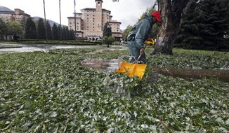 FILE - In this Aug. 6, 2018 file photo, Carlton Burton, an employee of the Broadmoor Hotel, shovels leaves and hail after a storm that damaged buildings, injured 14 people and killed at least five zoo animals in the Colorado Springs, Colo., area. Hailstorms inflict billions of dollars in damage yearly in North America alone, and the cost will rise as the growing population builds more homes, offices and factories, climate and weather experts said Tuesday, Aug. 14. The role of climate change in hailstorms is harder to assess, the experts said at a conference at the National Center for Atmospheric Research in Boulder. (Jerilee Bennett/The Gazette via AP)