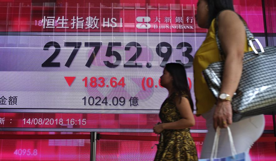 People walk past a bank electronic board showing the Hong Kong share index at Hong Kong Stock Exchange Wednesday, Aug. 15, 2018. Shares were mostly lower in Asia early Wednesday despite a rally overnight on Wall Street as investors' jitters over the Turkish currency crisis eased.(AP Photo/Vincent Yu)