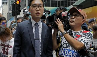 Pro-independence activist Andy Chan, left, is surrounded by journalists as he leaves Foreign Correspondents Club after delivering his speech in Hong Kong, Tuesday, Aug. 14, 2018. Chan gave a speech to foreign journalists whose association defied the Chinese government's demand to cancel the event. (AP Photo/Vincent Yu)