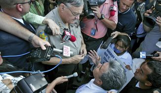FILE - In this July 14, 2006, file photo, Elias Bermudez kneels before then-Sheriff Joe Arpaio at a protest over the lawman's immigration crackdowns in Phoenix. Bermudez, who led the pro-immigrant group Immigrants Without Borders, is asking a judge to move his Sept. 5. 2018 trial on tax charges out of Arizona, citing publicity about the charges and his past advocacy efforts. He has pleaded not guilty to the charges. (AP Photo/Matt York, File)