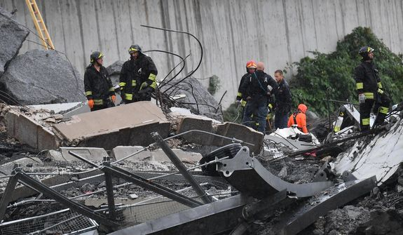 Rescues work among the rubble of the collapsed Morandi highway bridge in Genoa, northern Italy, Tuesday, Aug. 14, 2018. A large section of the bridge collapsed over an industrial area in the Italian city of Genova during a sudden and violent storm, leaving vehicles crushed in rubble below. (Luca Zennaro/ANSA via AP)