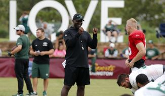 New York Jets head coach, Todd Bowles, center talks with quarterback Josh McCown (15) during the New York Jets Washington Redskins NFL football training camp in Richmond, Va., Monday, Aug. 13, 2018. (AP Photo/Steve Helber)