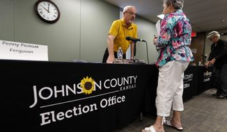 Board of County Commissioners 1st District Commissioner Ron Shaffer, left, talks with Barbara Holzmark, of Leawood, Kan., following the Johnson County Board of Canvassers meeting, Monday, Aug. 13, 2018, in Olathe, Kan. County election officials across Kansas on Monday began deciding which provisional ballots from last week's primary election will count toward the final official vote totals, with possibility that they could create a new leader in the hotly contested Republican race for governor. Secretary of State Kris Kobach led Gov. Jeff Colyer by a mere 110 votes out of more than 313,000 cast as of Friday evening. (AP Photo/Charlie Neibergall)