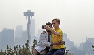 Adi Kang, left, and Brendon Walter take a photo together as a smoky haze obscures the Space Needle and downtown Seattle behind them, Tuesday, Aug. 14, 2018. Public-health officials are warning of unhealthy air across parts of the Pacific Northwest as smoke from wildfires move across the region. (AP Photo/Elaine Thompson)