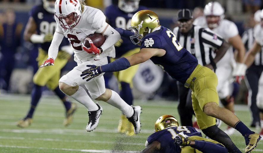 File- This Oct. 15, 2016, file photo shows Stanford wide receiver Trenton Irwin (2) leaping over Notre Dame safety Devin Studstill (14) as he's tackled by safety Drue Tranquill (23) during the first quarter of an NCAA college football game in South Bend, Ind. Notre Dame head football coach Brian Kelly thinks his players' familiarity with new defensive coordinator Clark Lea's defense will breed contempt for the opposition this fall. Tranquill, a rover last year, returns for his fifth season at weakside linebacker position. (AP Photo/Michael Conroy, File)