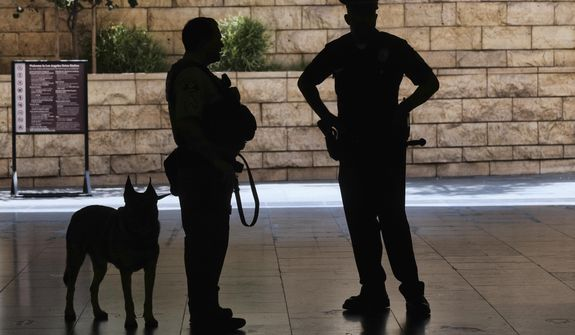 In this file photo, Los Angeles Metro Police and K-9 stand at the entrance to Union Station in Los Angeles on Tuesday, Aug. 14, 2018 prior to a news conference by The Transportation Security Administration (TSA) administrator David P. Pekoske. (AP Photo/Richard Vogel) **FILE**