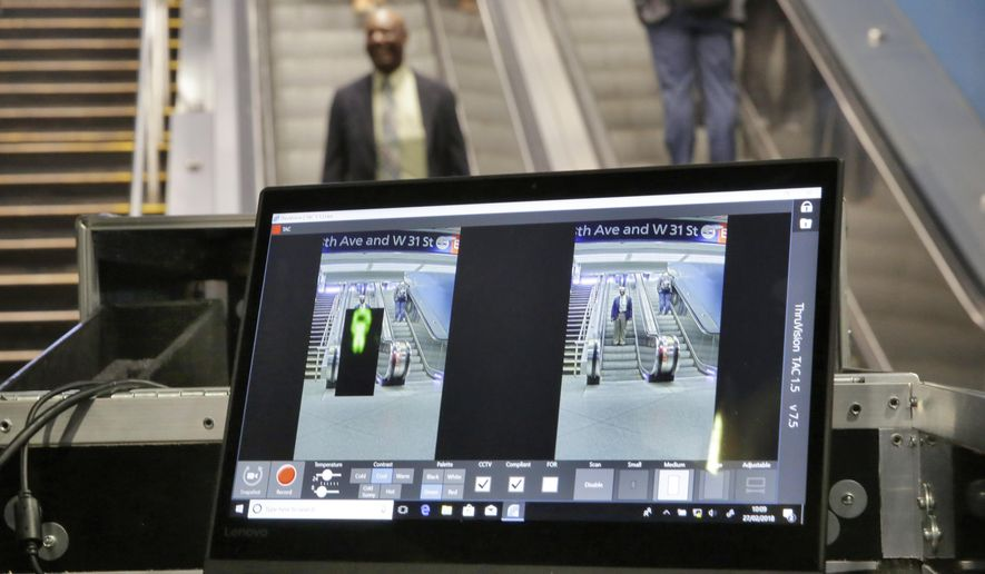 FILE - In this Tuesday, Feb. 27, 2018 file photo ThruVision suicide vest-detection technology reveals an suspicious object on a man, at left, during a Transportation Security Administration demonstration in New York's Penn Station. Los Angeles is poised to have the first mass transit system in the U.S. with body scanners that screen passengers for weapons and explosives. Officials from the Los Angeles County Metropolitan Transportation Authority and the Transportation Security Administration have scheduled a Tuesday, Aug. 14, 2018, news conference. The TSA has been working on the experimental devices, known as standoff explosive detection units, since 2004 with transit agencies. They hadn't been deployed permanently at any transit hub. (AP Photo/Richard Drew,File)
