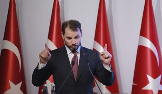 Berat Albayrak, Turkey's Treasury and Finance Minister, gestures as he talks during a conference in Istanbul, Friday, Aug. 10, 2018, in a bid to ease investor concerns about Turkey's economic policy. Albayrak said the government will safeguard the independence of the central bank and outlined his ministry's new economic policy as the currency plunged, raising questions about the country's financial stability. (AP Photo/Mucahid Yapici)