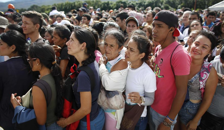 FILE - In this July 17, 2016 file photo, Venezuelans wait in line to cross into Colombia through the Simon Bolivar bridge in San Antonio del Tachira, Venezuela. The United Nations says an estimated 2.3 million Venezuelans had fled the country as of June 2018, mainly to Colombia, Ecuador, Peru and Brazil. (AP Photo/Ariana Cubillos, File)