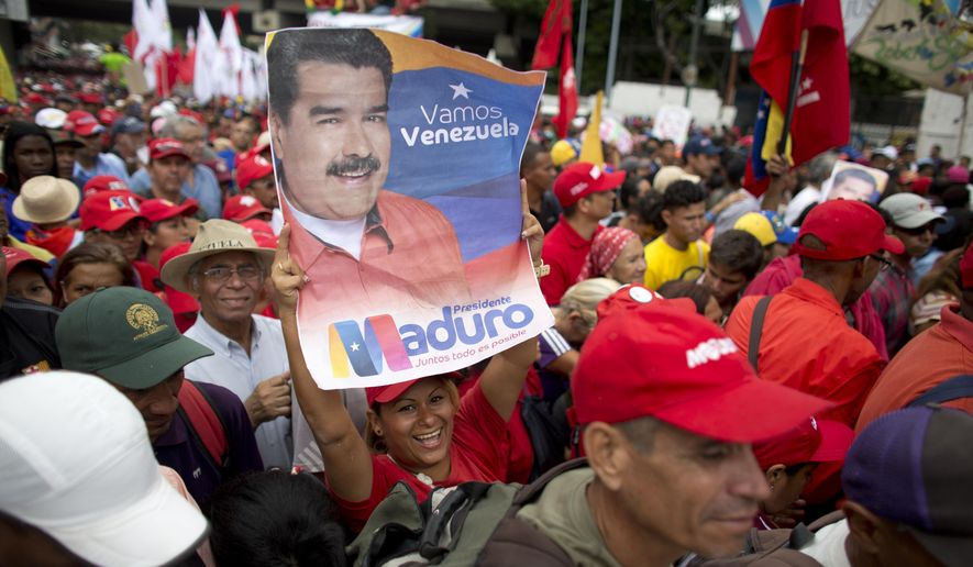 A supporter of Venezuela's President Nicolas Maduro holds up his picture during a rally in Caracas, Venezuela, Monday, Aug. 13, 2018. The United Socialist Party of Venezuela (PSUV) organized the rally to show support for the president following what the government called a failed assassination attempt with explosives-laden drones. (AP Photo/Ariana Cubillos)