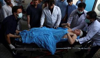 An injured man is put into an ambulance following a suicide bombing that targeted a training class in a private building in western Kabul, Afghanistan, on Wednesday. The public Health Ministry said there were at least 48 dead and dozens wounded. (ASSOCIATED PRESS)