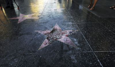 """FILE - This photo July 25, 2018 file photo shows Donald Trump's star on the Hollywood Walk of Fame that was vandalized, in Los Angeles. The man accused of smashing Trump's star says his actions were a """"rightful and just act."""" Austin Clay pleaded not guilty to a felony vandalism charge in Los Angeles, Wednesday, Aug. 15, 2018. (AP Photo/Reed Saxon, File)"""