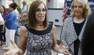 Rep. Martha McSally, R-Ariz., left, speaks to reporters after a news conference at a campaign event for her U.S. Senate primary race, as former Arizona Republican Gov. Jan Brewer, right, looks on Wednesday, Aug. 15, 2018, in Phoenix. McSally, Kelli Ward and former Maricopa County Sheriff Joe Arpaio are vying for the Republican nomination, but there are no plans currently for a televised debate for the Republican candidates, on the Democratic side, Rep. Kyrsten Sinema and activist Deedra Abboud haven't had a televised debate either. (AP Photo/Ross D. Franklin)