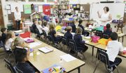 First graders in Caryn Bednarek's class at Queen of All Saints Catholic School enjoy a snack and listen quietly as she goes over their new classroom procedures on the first day of the 2018-2019 school year Wednesday, Aug. 15, 2018, in Michigan City, Ind. (Kelley Smith/The News-Dispatch via AP)