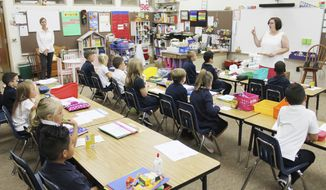 First-graders in Caryn Bednarek's class at Queen of All Saints Catholic School enjoy a snack and listen quietly as she goes over their new classroom procedures on the first day of the 2018-2019 school year Wednesday, Aug. 15, 2018, in Michigan City, Ind. (Kelley Smith/The News-Dispatch via AP) ** FILE **