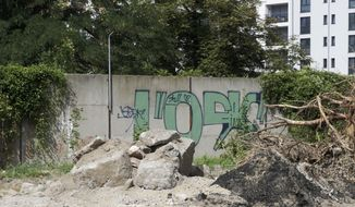 A newly discovered section of the Berlin Wall hides behind the bushes near the headquarters of Germany's Federal Intelligence Service in Berlin, Germany, Wednesday, Aug. 15, 2018. A local official has discovered a forgotten remnant of the Berlin Wall close to the new headquarters of Germany's foreign intelligence service. It's the second long-lost piece of the barrier to be identified and given protected status this year. (AP Photo/Miriam Karout)