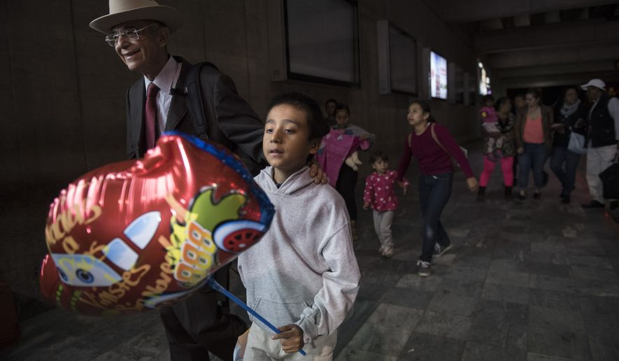 Anthony David Tovar Ortiz, center, is accompanied by attorney Ricardo de Anda after arriving to La Aurora airport in Guatemala City, Tuesday, Aug. 14, 2018. The 8-year-old stayed in a shelter for migrant children in Houston after his mother Elsa Ortiz Enriquez was deported in June 2018 under President Donald Trump administration's zero tolerance policy. (AP Photo/Oliver de Ros)