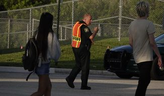A Broward County sheriff's deputy was on hand Wednesday as students arrived at Marjory Stoneman Douglas High School in Parkland, Florida, for the first day of classes. (Associated Press/File)