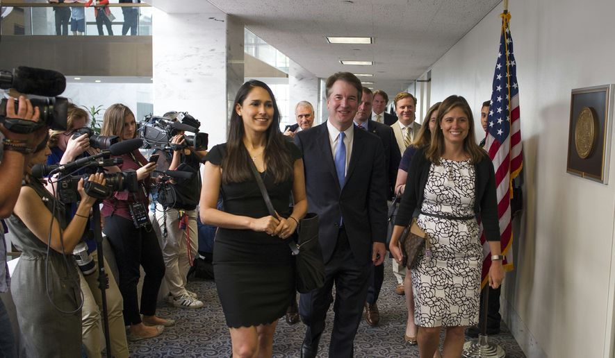 Supreme Court nominee Brett Kavanaugh, center, walks to the office of Sen. Heidi Heitkamp, D-N.D., for a meeting with her on Capitol Hill in Washington, Wednesday, Aug. 15, 2018. (AP Photo/Cliff Owen)