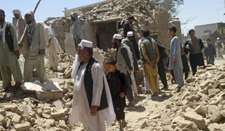 Afghan men stand near a damaged house following a Taliban attack in Ghazni, Afghanistan, Wednesday, Aug. 15, 2018. A Taliban assault on two adjacent checkpoints in northern Afghanistan killed at least 30 soldiers and police, officials said Wednesday. Life gradually returned to normal in parts of the eastern city of Ghazni after a massive insurgent attack last week, with sporadic gunbattles still underway in some neighborhoods. (AP Photo/Rahmatullah Nikzad)