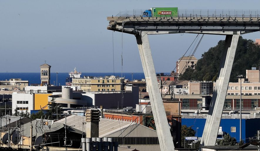 A view of the Morandi highway bridge that collapsed in Genoa, northern Italy, Wednesday, Aug. 15, 2018. A large section of the bridge collapsed over an industrial area in the Italian city of Genova during a sudden and violent storm, leaving vehicles crushed in rubble below. (AP Photo/Antonio Calanni)