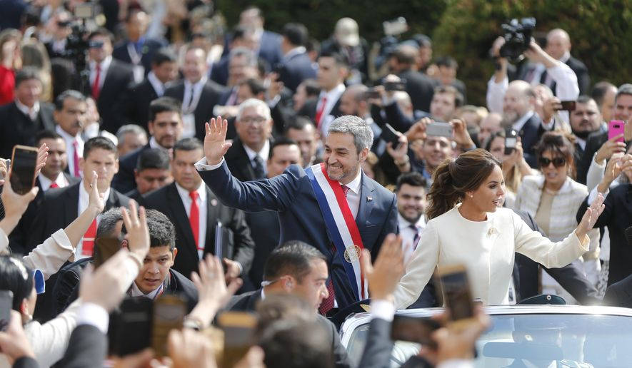 """Paraguay's new President Mario Abdo Benitez rides in an open top car with his wife Silvana Lopez, after his inauguration ceremony at """"Lopez Palace"""" in Asuncion, Paraguay, Wednesday, Aug. 15, 2018. (AP Photo/Jorge Saenz)"""