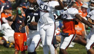 Chicago Bears linebacker Danny Trevathan leads teammates as they take part in drills during a joint NFL football training camp session against the Denver Broncos Wednesday, Aug. 15, 2018, at Broncos' headquarters in Englewood, Colo. (AP Photo/David Zalubowski)