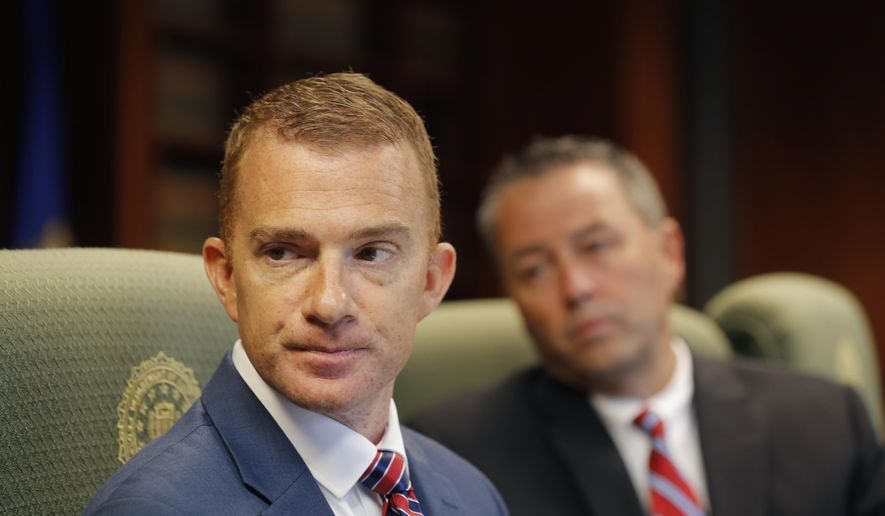 In this Tuesday, July 31, 2018, photo, FBI agent Matthew Ramey, who supervises their New Orleans field office's cyber squad, speaks during an interview with The Associated Press at their offices in New Orleans. Behind him is Drew Watts, an assistant special agent in charge. More than 20 people working for the FBI headquarters in Louisiana are working on cyber security. (AP Photo/Gerald Herbert)