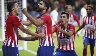 Atletico's Diego Costa, 2nd left celebrates with teammates after scoring his sides first goal during the UEFA Super Cup final soccer match between Real Madrid and Atletico Madrid at the Lillekula Stadium in Tallinn, Estonia, Wednesday, Aug. 15, 2018. (AP Photo/Pavel Golovkin)