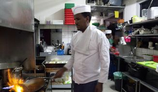 In this Wednesday, Aug. 8, 2018 photo, Eritrean migrant Russom Weldu Weldeslasie works at a restaurant in Tel Aviv, Israel. African migrants coming into Israel have been detained, threatened with deportation and faced hostility from lawmakers and residents. Now, they face another burden: a de facto 20 percent salary cut that has squeezed them financially and driven them further into poverty. (AP Photo/Caron Creighton)