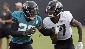 In this July 31, 2018, photo, Jacksonville Jaguars cornerback Jalen Ramsey (20) defends against receiver D.J. Chark Jr. during a practice at NFL football training camp in Jacksonville, Fla. Ramsey is making headlines from his couch. The Jaguars All-Pro cornerback is back in the news criticizing several NFL quarterbacks three days after being suspended for screaming obscenities at reporters. (AP Photo/John Raoux)