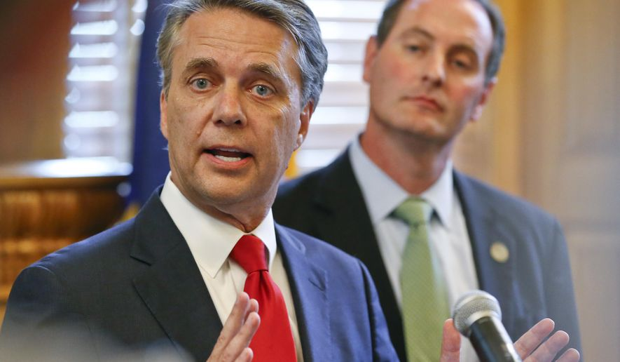 FILE - In this Aug. 8, 2018, file photo, Kansas Gov. Jeff Colyer, left, alongside Lt. Gov. Tracey Mann, addresses the media at the Kansas Statehouse in Topeka, Kan., a day after his primary race against Kansas Secretary of State Kris Kobach. Colyer conceded late Tuesday, Aug. 14, 2018, in the state's Republican gubernatorial primary, saying he will endorse Kobach a week after their neck-and-neck finish threatened to send the race to a recount. (Chris Neal/The Topeka Capital-Journal via AP, File)