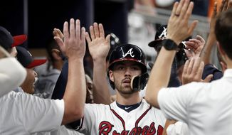 Atlanta Braves' Dansby Swanson is congratulated in the dugout after hitting a two-run home run during the fourth inning against the Miami Marlins in a baseball game Wednesday, Aug. 15, 2018, in Atlanta. (AP Photo/John Bazemore)