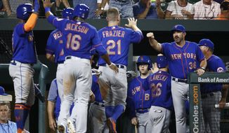New York Mets manager Mickey Callaway, right, greets Todd Frazier (21) after Frazier scored on Kevin Plawecki's grand slam during the sixth inning of a baseball game against the Baltimore Orioles, Wednesday, Aug. 15, 2018, in Baltimore. (AP Photo/Patrick Semansky)