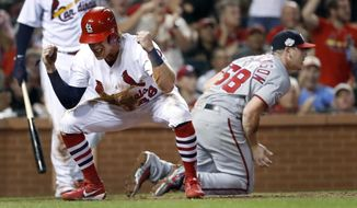 St. Louis Cardinals' Harrison Bader, left, celebrates on a wild pitch by Washington Nationals starting pitcher Jeremy Hellickson (58) during the fifth inning of a baseball game Wednesday, Aug. 15, 2018, in St. Louis. Hellickson was injured on the play and left the game. (AP Photo/Jeff Roberson)