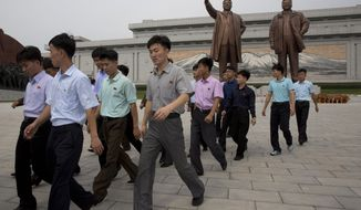 Men leave after paying their respects before the giant bronze statues of late North Korean leaders Kim Il Sung and his son Kim Jong Il during the anniversary of the end of World War II and the country's liberation from Japanese colonial rule in Pyongyang, North Korea Wednesday, Aug. 15, 2018. North Korea has marked the anniversary with a series of ceremonies ahead of what is expected to be a much bigger event next month, the 70th anniversary of its national foundation day. (AP Photo/Ng Han Guan)