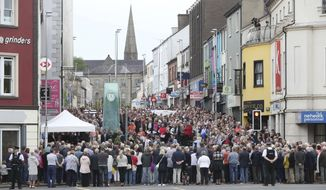 People gather in the market town of Omagh, Northern Ireland, Wednesday Aug. 15, 2018, during a ceremony to mark the 20th anniversary of the Omagh bombing on Aug. 15, 1998, with the glass Omagh Bomb Memorial, centre left.  Bereaved families are marking the 20th anniversary of the deadliest attack in Northern Ireland's four decades of violence, which left 29 people dead, including a woman pregnant with twins. (Niall Carson/PA via AP)