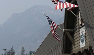 U.S. flags fly in smoke-filled air, Wednesday, Aug. 15, 2018, at Snoqualmie Pass in Washington state. Public-health officials continued to warn of unhealthy air across many parts of the Pacific Northwest as wildfires sent thick smoke across the region, and the National Weather Service issued an air quality alert for much of Central and Eastern Washington and northern Idaho through Wednesday. (AP Photo/Ted S. Warren)