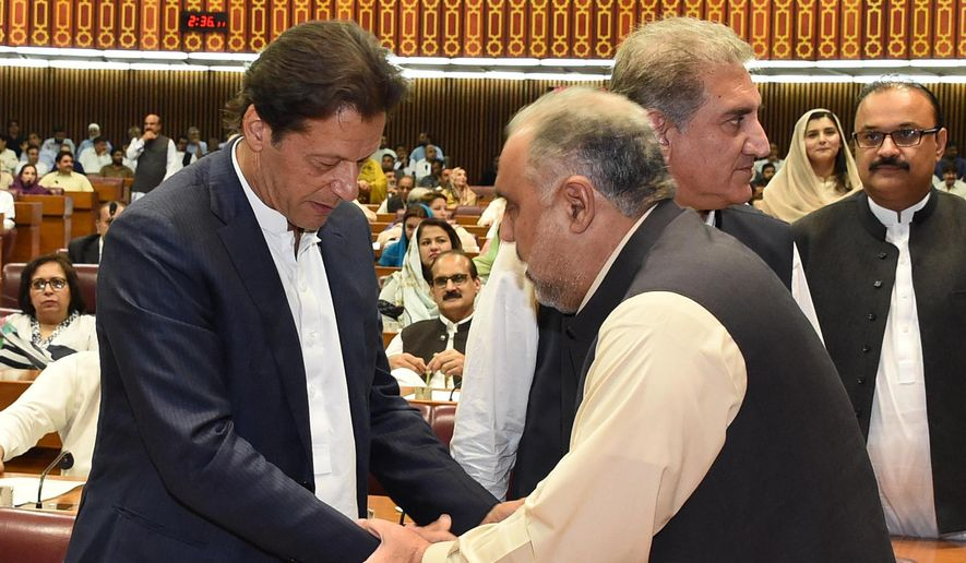In this photo released by the National Assembly, the leader of Pakistan Tahreek-e-Insaf party Imran Khan, left, greets speaker of the National Assembly Asad Qaiser in Islamabad, Pakistan, Wednesday, Aug. 15, 2018. (National Assembly, via AP)