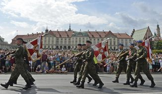 Polish Army soldiers holding military unit banners march on one of the city's main streets during a yearly military parade celebrating the Polish Army Day in Warsaw, Poland, Wednesday, Aug. 15, 2018, with the Royal Castle in the background. (AP Photo/Alik Keplicz)