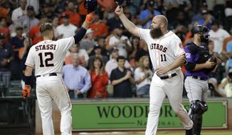 Houston Astros' Evan Gattis (11) celebrates with Max Stassi (12) after hitting a home run during the fifth inning of a baseball game against the Colorado Rockies on Wednesday, Aug. 15, 2018, in Houston. (AP Photo/David J. Phillip)