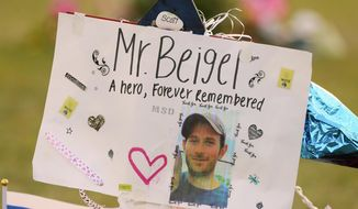 """This Feb. 20, 2018, file photo shows a memorial for Geography teacher and cross-country coach, Scott Beigel at Pine Trails Park in Parkland, Fla. A street in New York's Long Island has been named for Beigel who helped shield students from the gunman in last winter's school shooting. The street where Beigel grew up in Dix Hills, N.Y., was dedicated """"Scott J. Beigel Way"""" on Saturday Aug. 11. (Mike Stocker/South Florida Sun-Sentinel via AP, File)"""