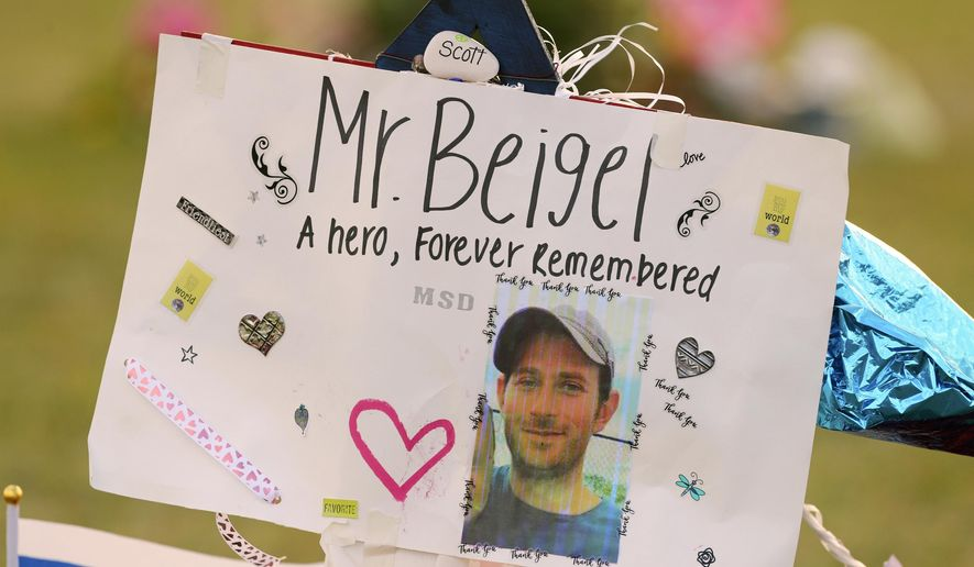 "This Feb. 20, 2018, file photo shows a memorial for Geography teacher and cross-country coach, Scott Beigel at Pine Trails Park in Parkland, Fla. A street in New York's Long Island has been named for Beigel who helped shield students from the gunman in last winter's school shooting. The street where Beigel grew up in Dix Hills, N.Y., was dedicated ""Scott J. Beigel Way"" on Saturday Aug. 11. (Mike Stocker/South Florida Sun-Sentinel via AP, File)"