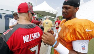 Tampa Bay Buccaneers quarterback Jameis Winston looks at a fan's jersey with his name printed upside down before he autographs it after a combined NFL football training camp practice with the Tennessee Titans Wednesday, Aug. 15, 2018, in Nashville, Tenn. (AP Photo/Mark Humphrey)