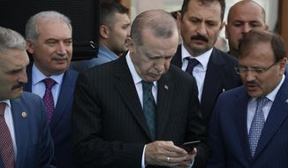 FILE - In this Friday, May 4, 2018 file photo, Turkey's President Recep Tayyip Erdogan, center, looks at his phone during a ceremony in Istanbul. Erdogan said Tuesday, Aug. 18, 2018, that his country will boycott U.S.-made electronic goods amid a diplomatic spat that has helped trigger a Turkish currency crisis. Showing no signs of backing down in the standoff, Erdogan suggested that Turkey would stop procuring U.S.-made Iphones and buy Korean Samsung or Turkish-made Vestel instead. (AP Photo/Lefteris Pitarakis, File)